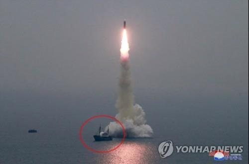 这是朝鲜试射新型潜射弹道导弹的现场照。用红圈标出的是朝鲜可能用于牵引驳船的船舶。 韩联社/朝中社(图片仅限韩国国内使用,严禁转载复制)