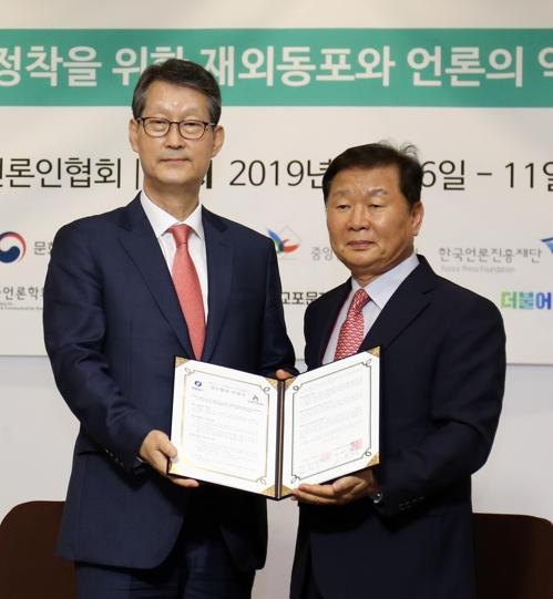 韩联社社长赵成富(左)与世界韩媒人协会会长全庸彰签署业务合作协议后合影。 韩联社