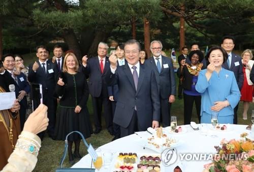 10月18日下午,在青瓦台,文在寅(右二)同各国驻韩外交使团摆爱心手势。 韩联社