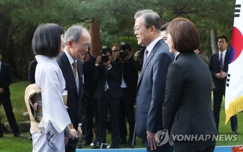 10月18日下午,在青瓦台,文在寅(右二)在驻韩外交使团招待会上同日本驻韩大使长岭安政(左二)互致问候。 韩联社