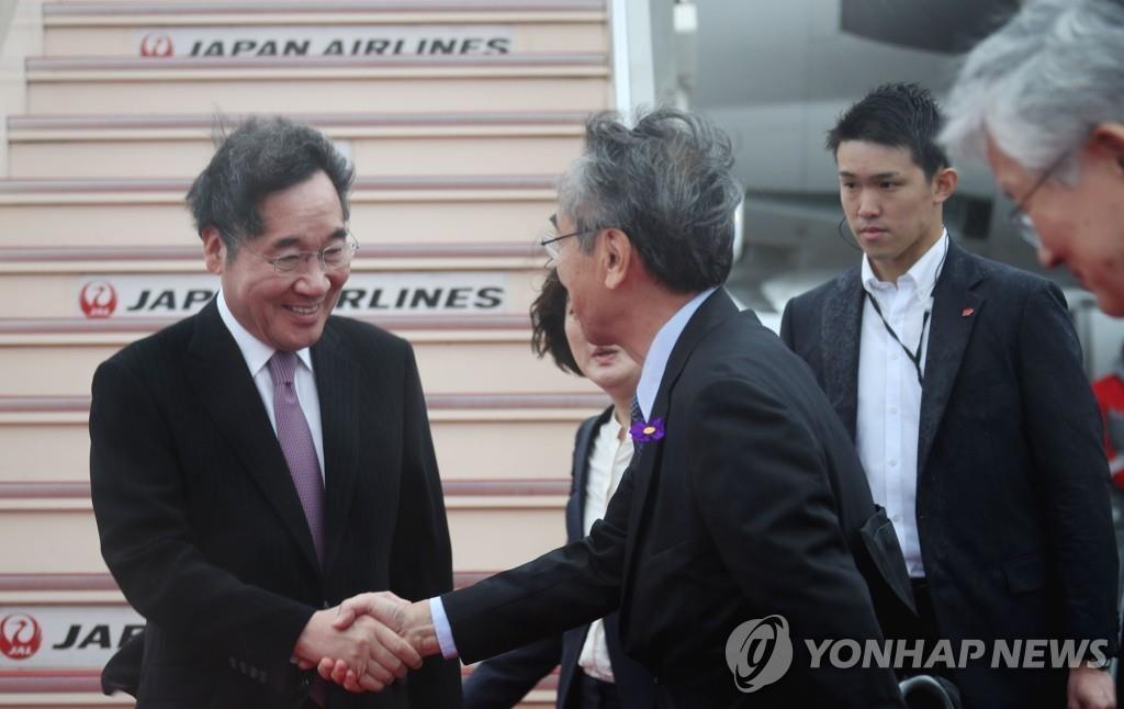 10月22日,韩国国务总理李洛渊(左)乘机抵达日本羽田机场,并同前来迎接的日方人士握手致意。他将出席当天下午在东京皇居举行的日本新国王德仁即位仪式。 韩联社