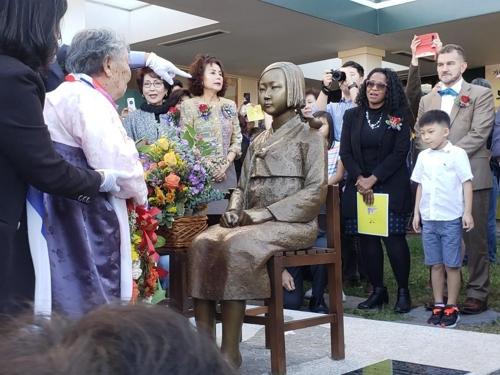 韩国慰安妇受害者吉元玉老人为和平少女像戴上花环。 韩联社