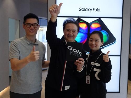 11月8日上午,三星电子上海南京东路旗舰店,一名顾客(居中)在购买三星Galaxy Fold后与工作人员合影。 韩联社