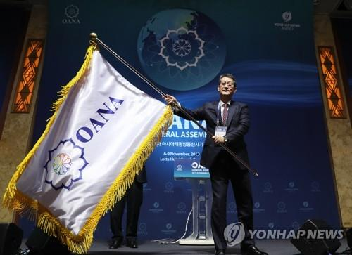 11月8日,在首尔乐天酒店,韩联社社长赵成富挥舞亚通组织旗帜。 韩联社
