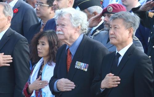 11月11日上午,在釜山联合国纪念公墓,文森特·库尔特奈尔(前排右二)向国旗敬礼。 韩联社