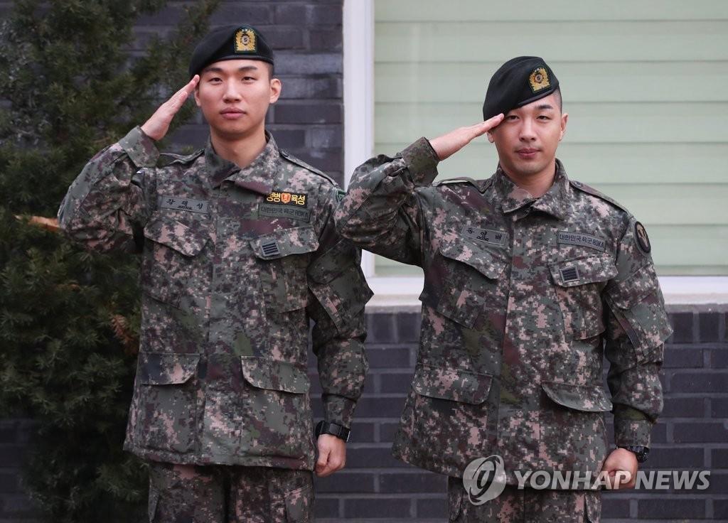11月10日,在京畿道龙仁市地面作战司令部前,BIGBANG成员太阳(右)和大成敬军礼。当天,二人正式退伍。 韩联社