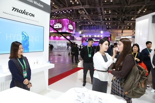 """11月26日上午,由韩国中小风险企业部主办的""""韩国美容展""""在釜山会展中心举行。图为访客体验韩国美妆。 韩联社"""