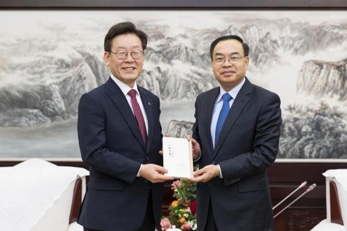 11月27日,在重庆,韩国京畿道知事李在明(左)与中国重庆市市长唐良智互换礼物。 韩联社/京畿道供图(图片严禁转载复制)