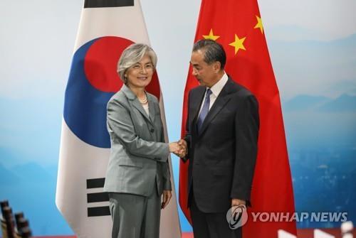 资料图片:8月20日,在北京,康京和(左)与王毅握手合影。 韩联社/外交部供图(图片严禁转载复制)