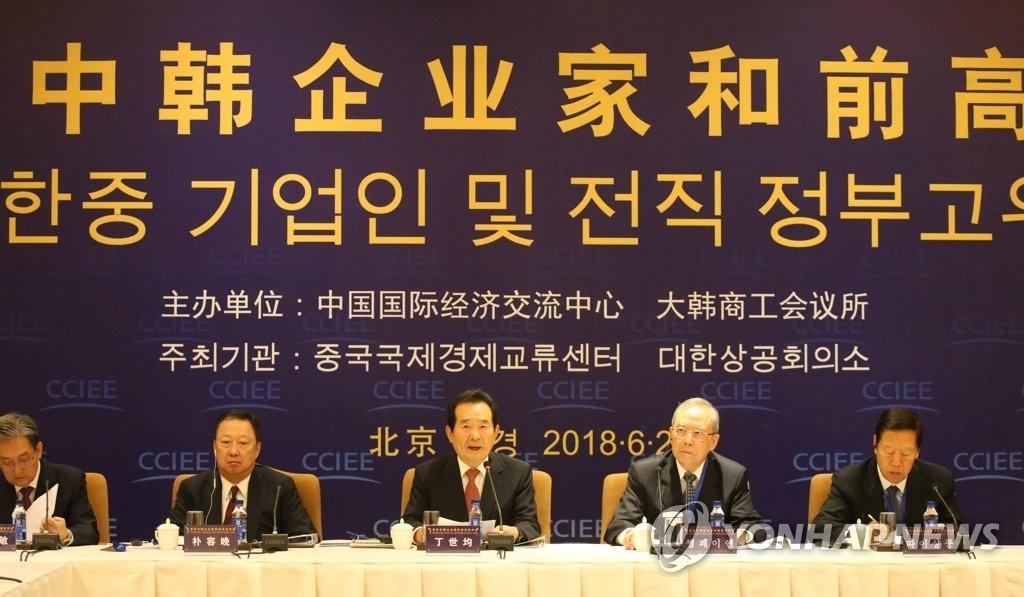 资料图片:2018年6月29日上午,在北京,韩国前国会议长丁世均(中)在首轮韩中企业家和前高官对话上致辞。韩联社