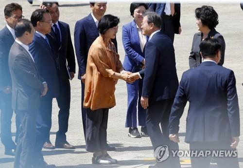 资料图片:2018年7月8日,在京畿道城南市首尔机场,文在寅在出访前与时任共同民主党党首秋美爱握手。 韩联社