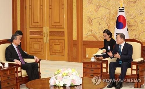 12月5日下午,在青瓦台,韩国总统文在寅(右)会见到访的中国国务委员兼外交部长王毅。 韩联社