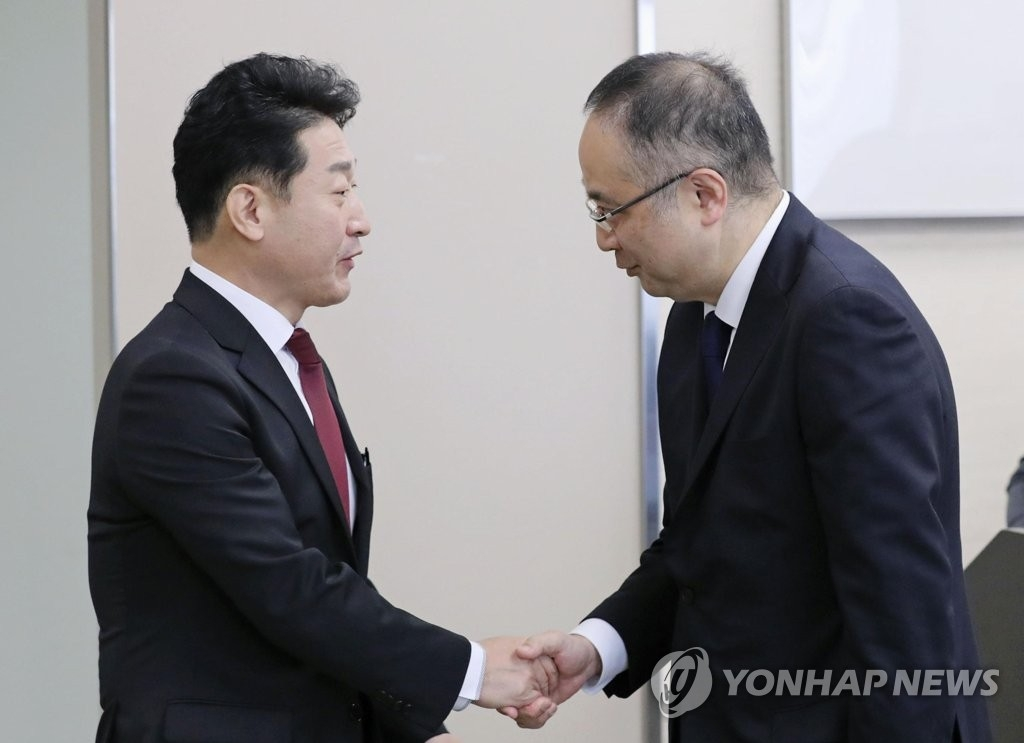 资料图片:12月17日,在日本经济产业省,出席韩日出口管理政策对话会的韩国产业通商资源部贸易政策局长李浩铉(左)和日本经济产业省贸易管理部长饭田阳一握手致意。 韩联社