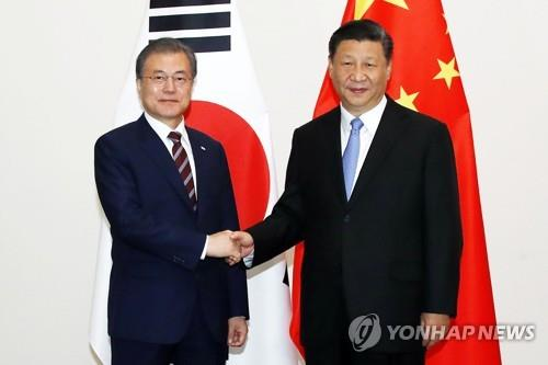 资料图片:2019年6月27日,在日本大阪,韩国总统文在寅(左)同中国国家主席习近平握手合影。 韩联社