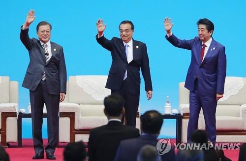 资料图片:12月24日,在成都,韩中日领导人共同出席工商峰会并挥手致意。左起依次是韩国总统文在寅、中国国务院总理李克强、日本首相安倍晋三。 韩联社