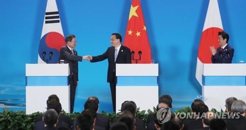 12月24日,在成都,韩中日领导人共同会见记者。左起依次是韩国总统文在寅、中国国务院总理李克强、日本首相安倍晋三。 韩联社