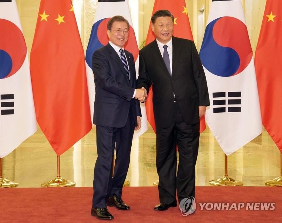 资料图片:12月23日,在北京,韩国总统文在寅(左)与中国国家主席习近平握手合影。 韩联社