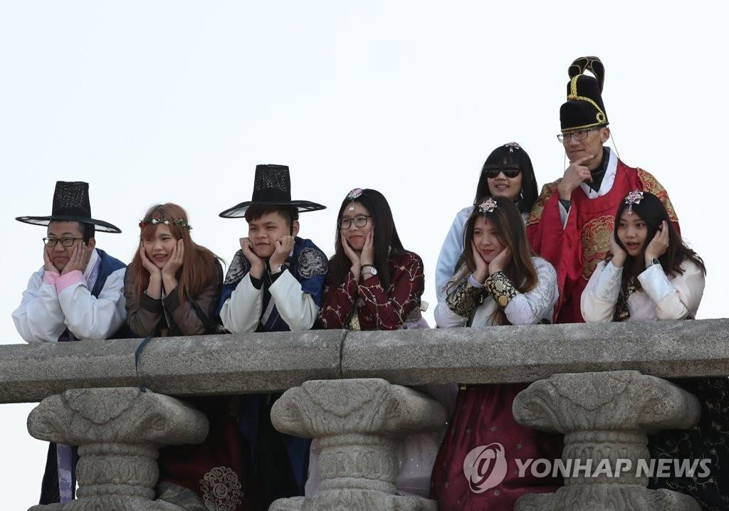 资料图片:访韩外国游客在首尔景福宫合影留念。 韩联社