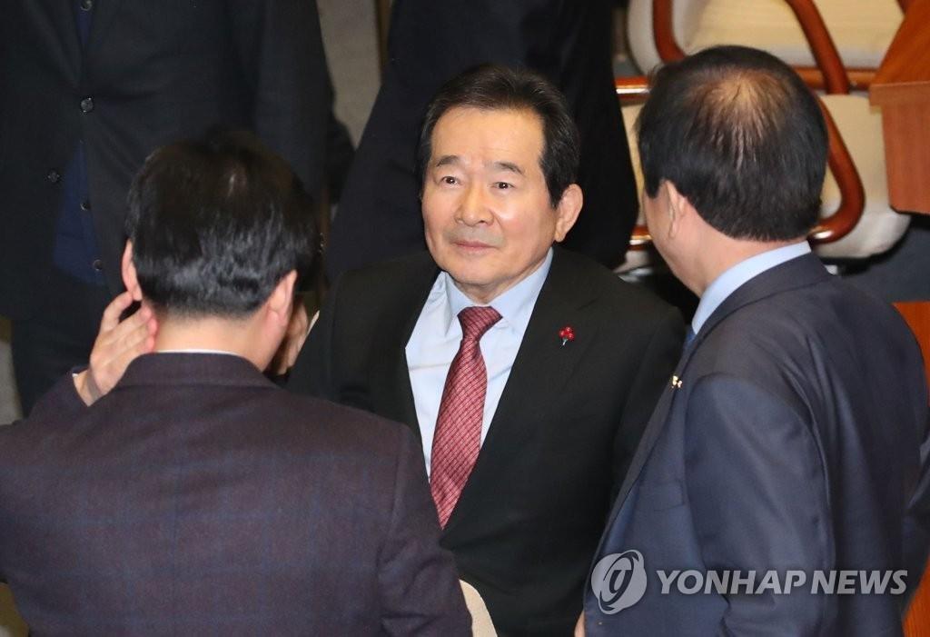 1月13日,在韩国国会,丁世均在任命案表决前与共同民主党议员交谈。 韩联社