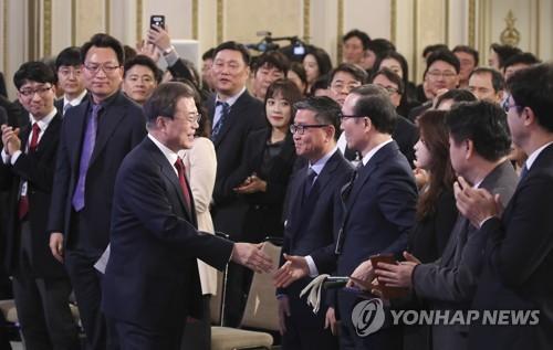 1月14日上午,在青瓦台迎宾馆,韩国总统文在寅举行新年记者会与在场人士握手致意。 韩联社