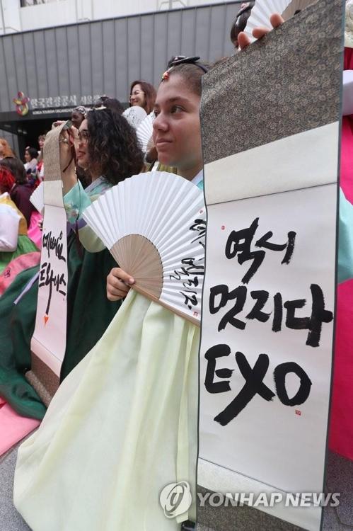 资料图片:2019年8月6日,在位于首尔中区的韩国观光公社大楼前,参加K-POP主题游的法国游客手举偶像应援字幅合影留念。 韩联社