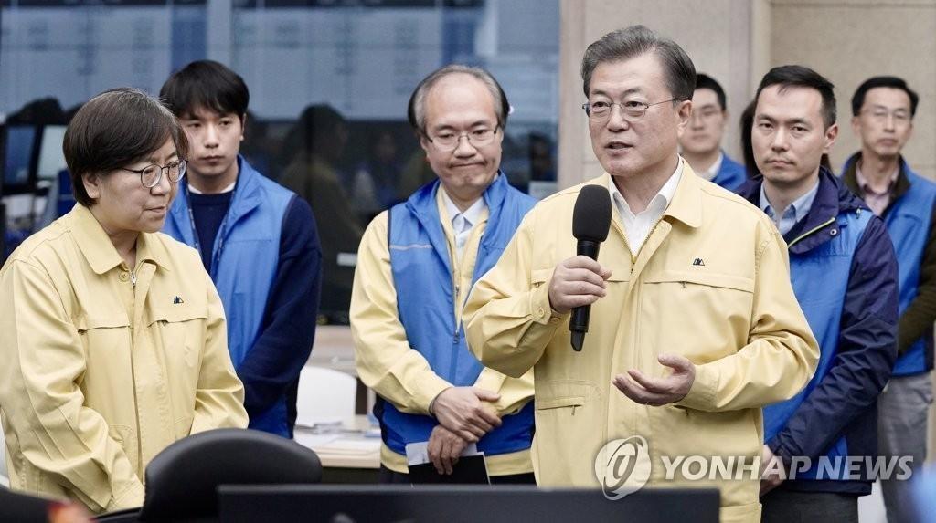 资料图片:3月11日下午,韩国总统文在寅(右)访问位于忠清北道清州市的疾病管理本部。 韩联社