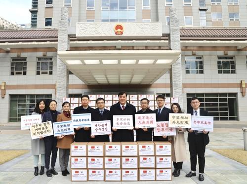 中国驻韩大使馆3月12日表示,向首尔市捐赠2.5万只KF94口罩。左六为中国驻韩大使邢海明。 韩联社/中国驻韩大使馆供图(图片严禁转载复制)