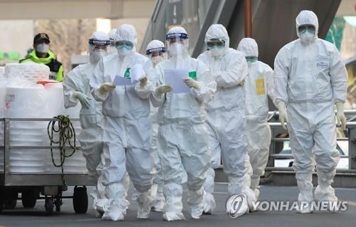 资料图片:3月24日,在位于大邱市的启明大学东山医院,全副武装的医务人员正走向负压病房。 韩联社