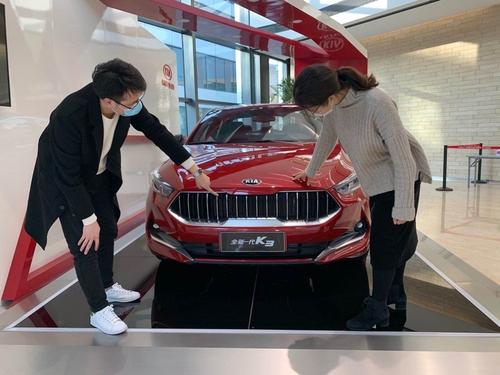 资料图片:东风悦达起亚工作人员给顾客介绍K3。 韩联社/现代汽车集团供图(图片严禁转载复制)