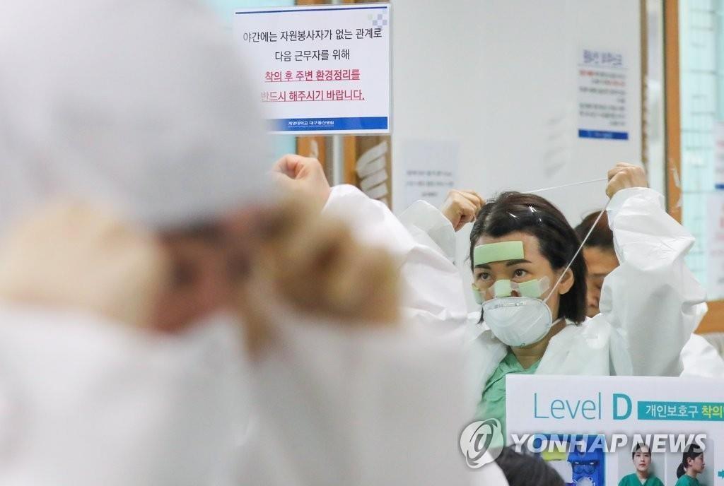 资料图片:4月9日,在位于大邱市的启明大学东山医院,医护人员身穿防护服准备战疫。 韩联社