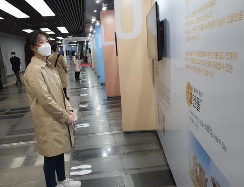 """4月22日,在首尔市龙山区,访客们观看""""2020年国家形象UP展览会""""。 韩联社"""