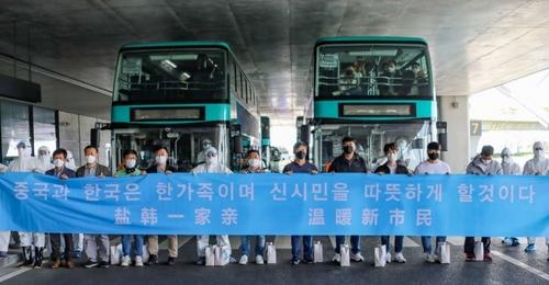 5月22日,在盐城机场,中国防疫人员欢迎走快捷通道的韩企人员。 韩联社