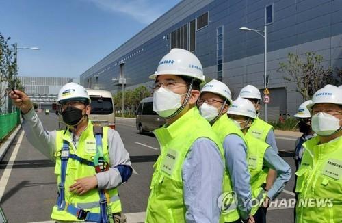 资料图片:5月18日,三星电子副会长李在镕(左二)视察旗下位于中国西安的半导体生产工厂。 韩联社/三星电子供图(图片严禁转载复制)