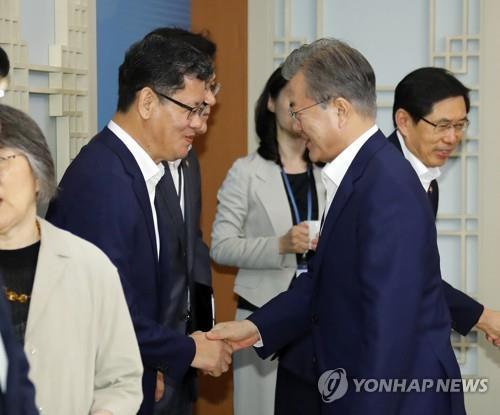 资料图片:2019年6月16日,在青瓦台,文在寅(右)与金炼铁握手致意。 韩联社