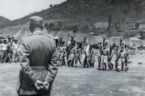 """这张照片拍摄于1951年6月的巨济俘虏收容所,囚犯们脱去上衣享受""""马背战争""""游戏带来的乐趣。 韩联社/ICRC供图(图片严禁转载复制)"""