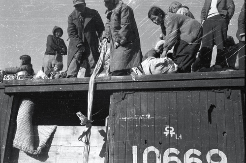 该照片拍摄于1950年12月29日的大邱,难民们正在爬上火车。 韩联社/ICRC供图(图片严禁转载复制)
