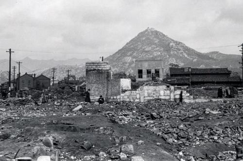被战争摧毁的首尔市中心。1951年首尔市中心遭受炮击,所有的建筑物都被破坏变为一片废墟,可看到在街上行走的市民。 韩联社/ICRC供图(图片严禁转载复制)