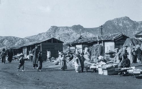 这张照片中记录了那些在战争废墟中为了维持生计摆摊做生意的市民。可以看到包括穿着韩服的小女孩在内,共有6-7名儿童在摊位前玩耍。 韩联社/ICRC供图(图片严禁转载复制)