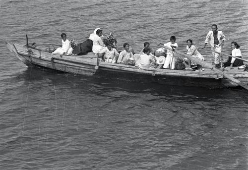 在大邱地区的某条江上,难民们乘坐渡船。一个儿童划桨的场景引人注目。 韩联社/ICRC供图(图片严禁转载复制)