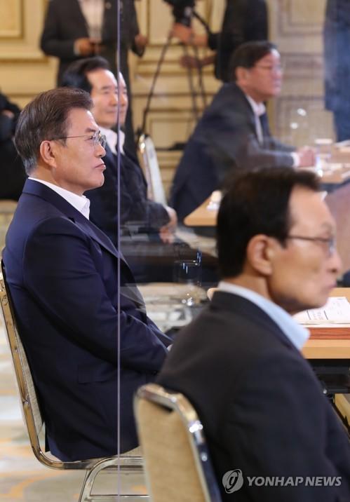 """7月14日,在青瓦台,韩国总统文在寅(左)在""""韩版新政""""综合规划国民报告大会上听取郑义宣汇报。 韩联社"""