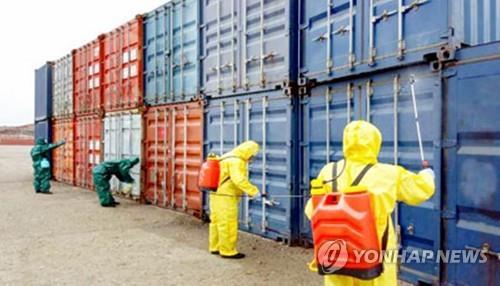 资料图片:3月9日,朝鲜防疫人员在南浦进出口货物检疫所对货物进行消毒,以防止新型冠状病毒传播至境内。 韩联社/《劳动新闻》官网截图(图片仅限韩国国内使用,严禁转载复制)