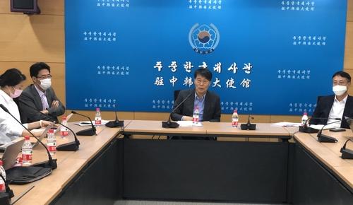 资料图片:7月27日,在北京,韩国驻华大使张夏成(中)向韩国记者介绍与中方就签证事宜进行磋商的结果。 韩联社