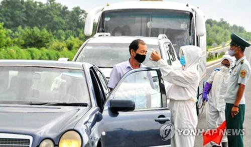 平壤市万景台区的医务人员为过路司机检测体温。 韩联社/《劳动新闻》截图(图片仅限韩国国内使用,严禁转载复制)