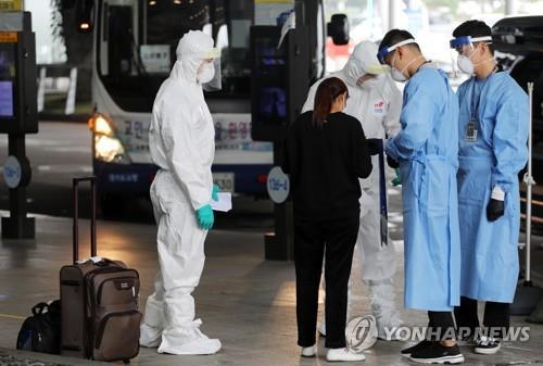 资料图片:7月27日,在仁川国际机场,防疫工作人员为外籍旅客提供交通指引。 韩联社