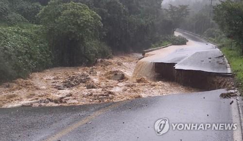 8月2日,位于忠清北道忠州市山尺面的一条道路被暴雨冲毁。 韩联社