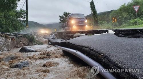 资料图片:8月3日,在江原道铁原郡,一处公路被塌陷。 韩联社