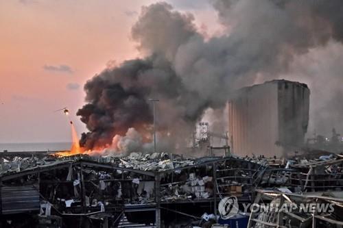 资料图片:当地时间8月4日,黎巴嫩首都贝鲁特港口发生大爆炸,图为直升机在事故现场空中灭火。 韩联社/法新社(图片严禁转载复制)