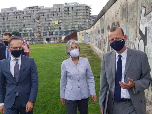 资料图片:当地时间8月10日,韩国外交部长官康京和(中)和德国外长海科·马斯(左)访问柏林墙公园。 韩联社