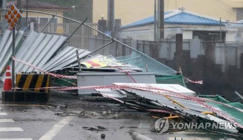 """资料图片:台风""""巴威""""吹倒安全围栏。 韩联社"""
