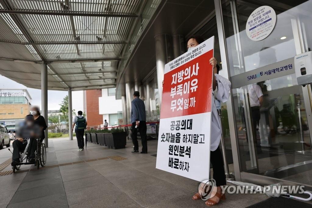 资料图片:8月27日,在首尔大学医院门口,实习医生们手举标牌反对政府扩招。 韩联社